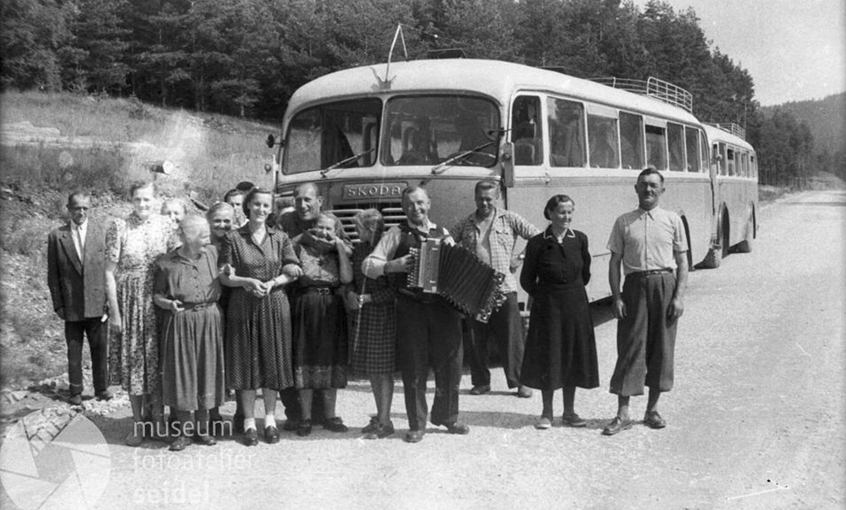 People in front of an old Škoda bus